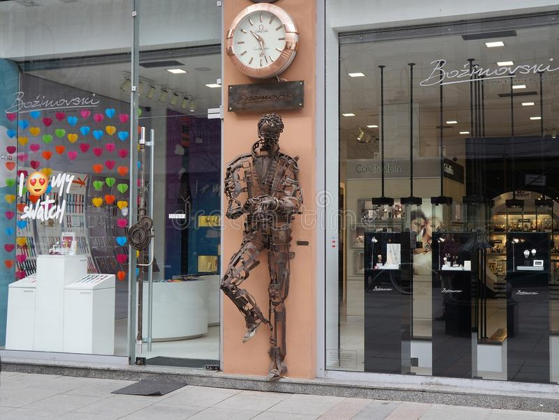 Sculpture of man checking time made of recycled metal pieces royalty free stock images