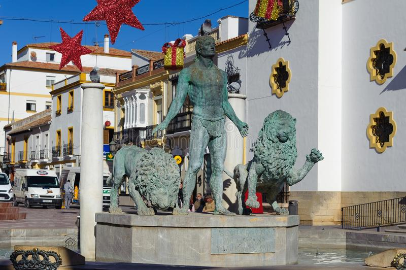 Sculpture of man with lions at central square of town decorated with Christmas toys. RONDA, SPAIN - DECEMBER 2017: Sculpture of man with lions at central square royalty free stock image