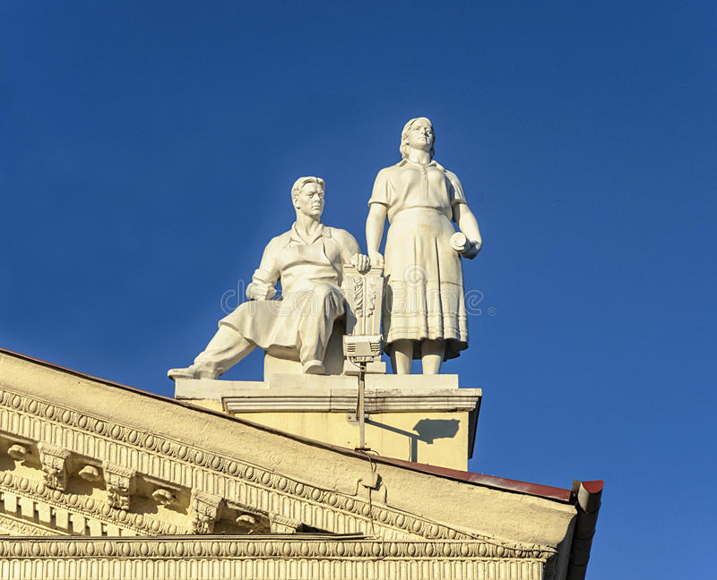 Sculpture of man and women on the roof of Trade Union Palace in stock photos
