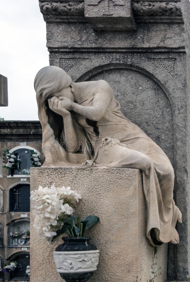 Sculpture of mourning crying woman on a grave royalty free stock photo