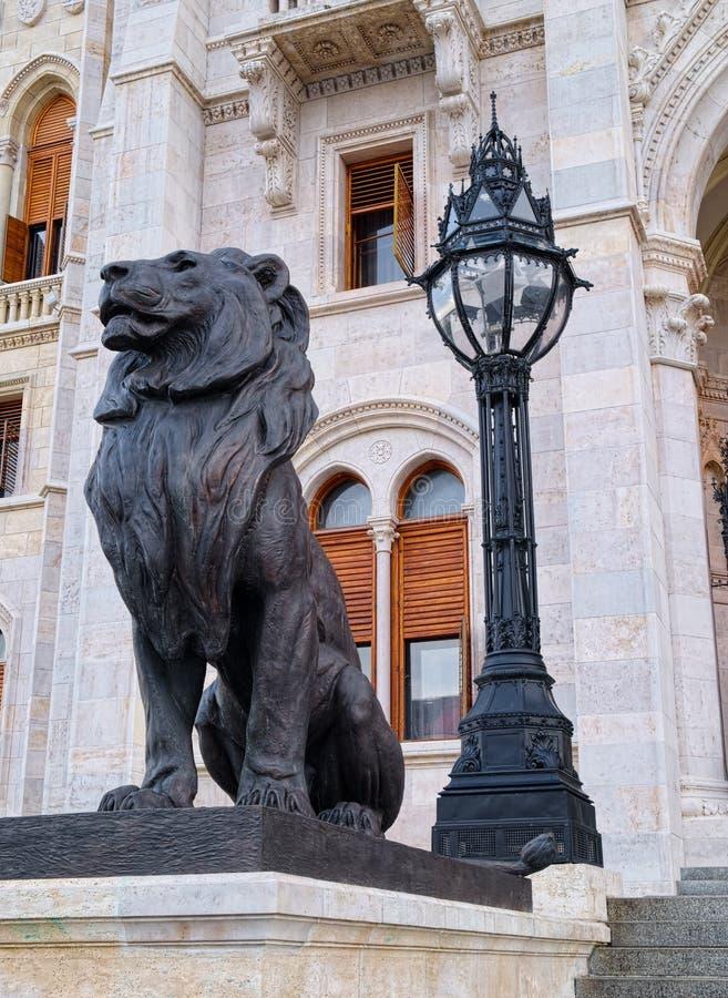 Sculpture noire de lion et lanterne noire derrière images libres de droits