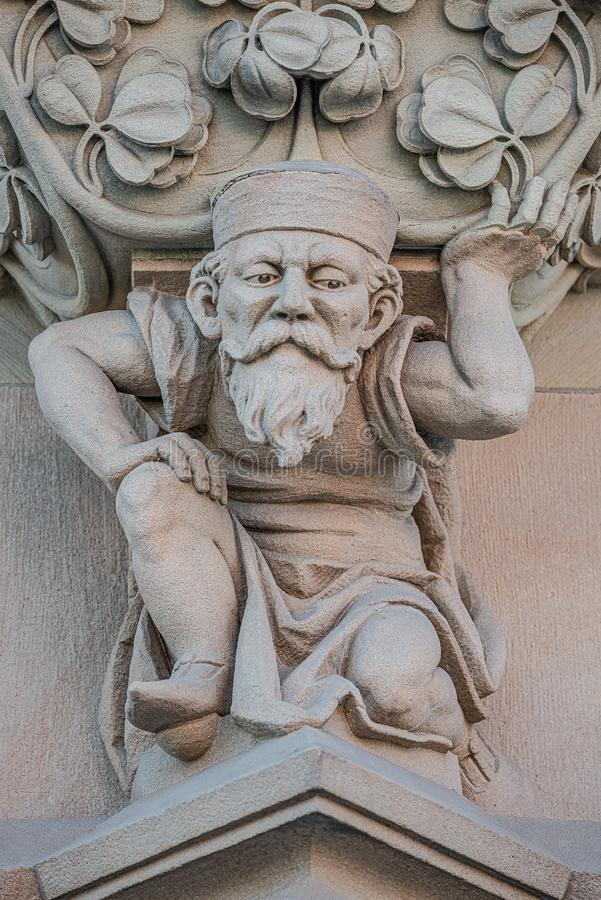 Sculpture of an old small and bearded funny man, dwarf, as an atlant in downtown of Magdeburg, Germany, closeup, details. Sculpture of an old small and bearded stock photography