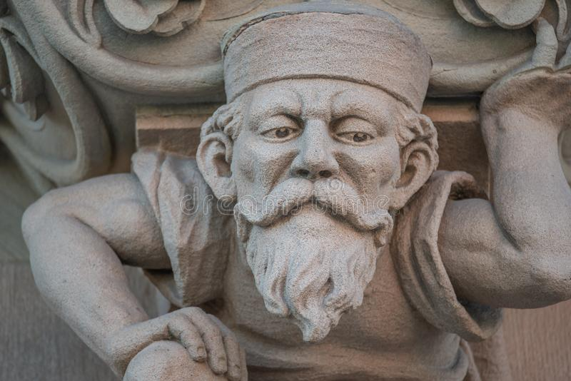Sculpture of an old small and bearded funny man, dwarf, as an atlant in downtown of Magdeburg, Germany, closeup, details. Sculpture of an old small and bearded stock photo