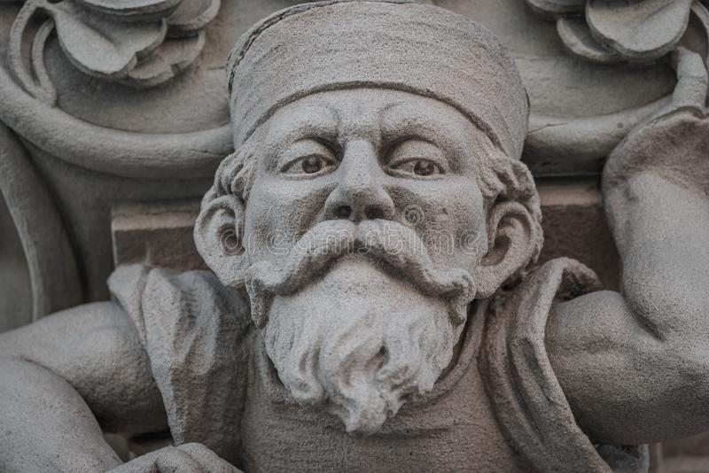 Sculpture of an old small and bearded funny man, dwarf, as an atlant in downtown of Magdeburg, Germany, closeup, details. Sculpture of an old small and bearded stock photos