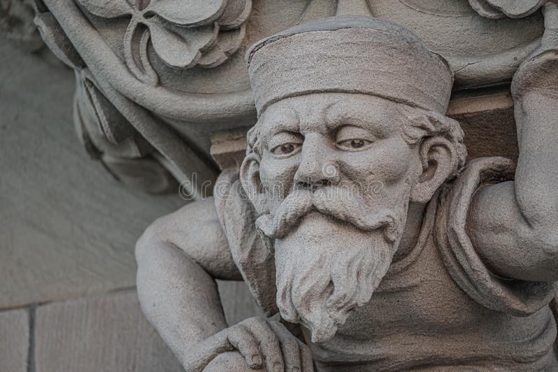 Sculpture of an old small and bearded funny man, dwarf, as an atlant in downtown of Magdeburg, Germany, closeup, details. Sculpture of an old small and bearded stock image