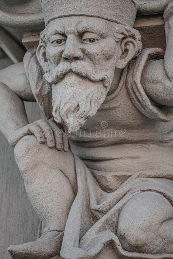 Sculpture of an old small and bearded funny man, dwarf, as an atlant in downtown of Magdeburg, Germany, closeup, details. Sculpture of an old small and bearded royalty free stock photography