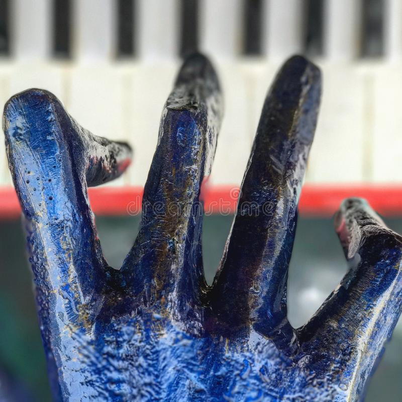 A blue hand plays a piano. A sculpture of a pianist plays a metal instrument with relish royalty free stock photos