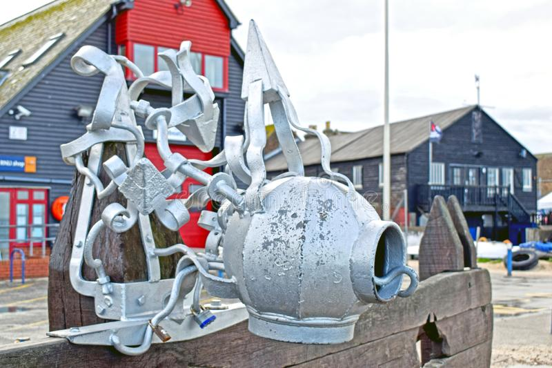 A sculpture in the shape of a diver`s hat in front of some buildings. A sliver coloured metal sculpture of a divers hat in front of Royal National Lifeboat stock photography