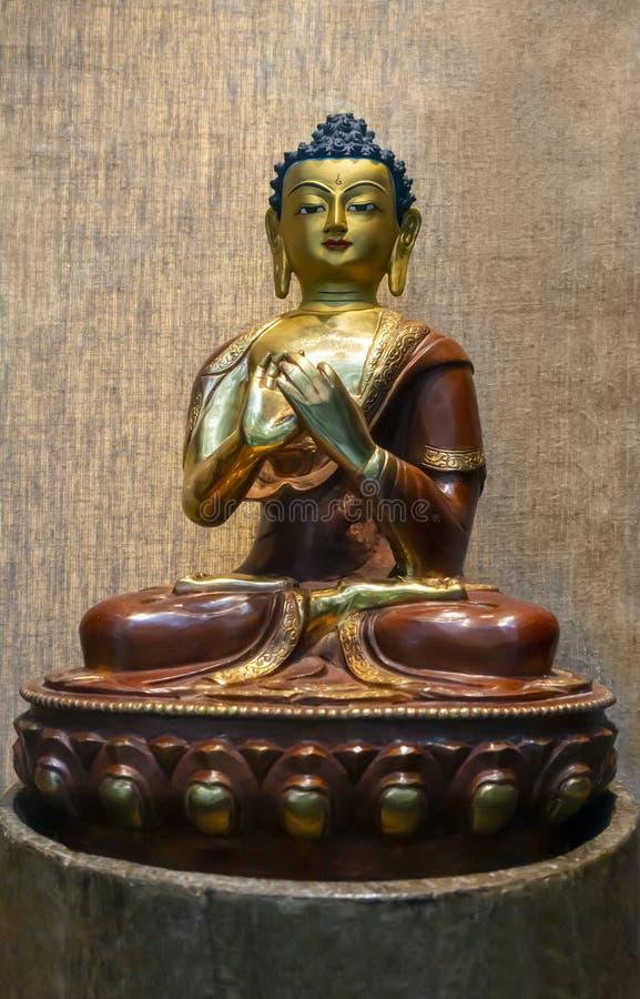 Sculpture Siddhartha Gautama -Sanskrit gold dark red orange coloring. Gold deep red sculpture of Amitabha Buddha Siddhartha Gautama sculpture praying hands lived royalty free stock images