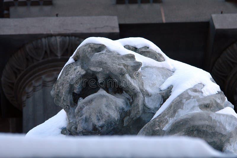 Sculpture of a sleeping lion under snow stock photo