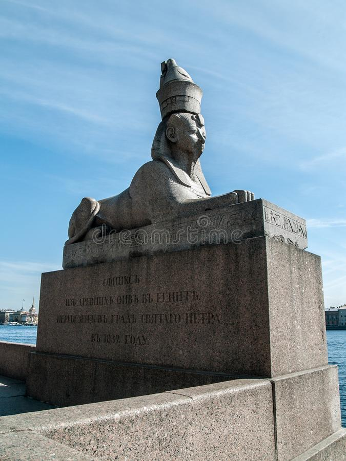 Sculpture of a stone sphinx on a pedestal on a granite embankment against a blue sky in St. Petersburg stock images