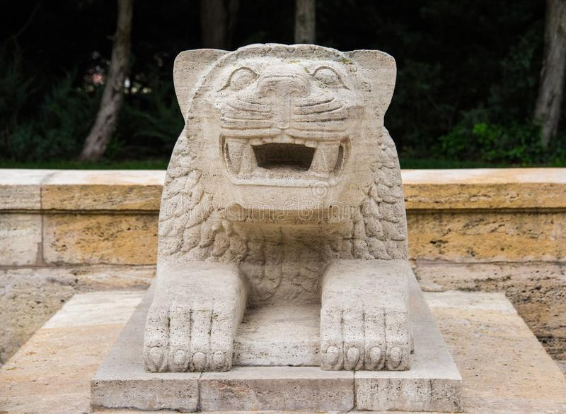 Stone decorative lion with open mouth. A sculpture of a stylized lion sitting down as a architectonic decoration stock photo