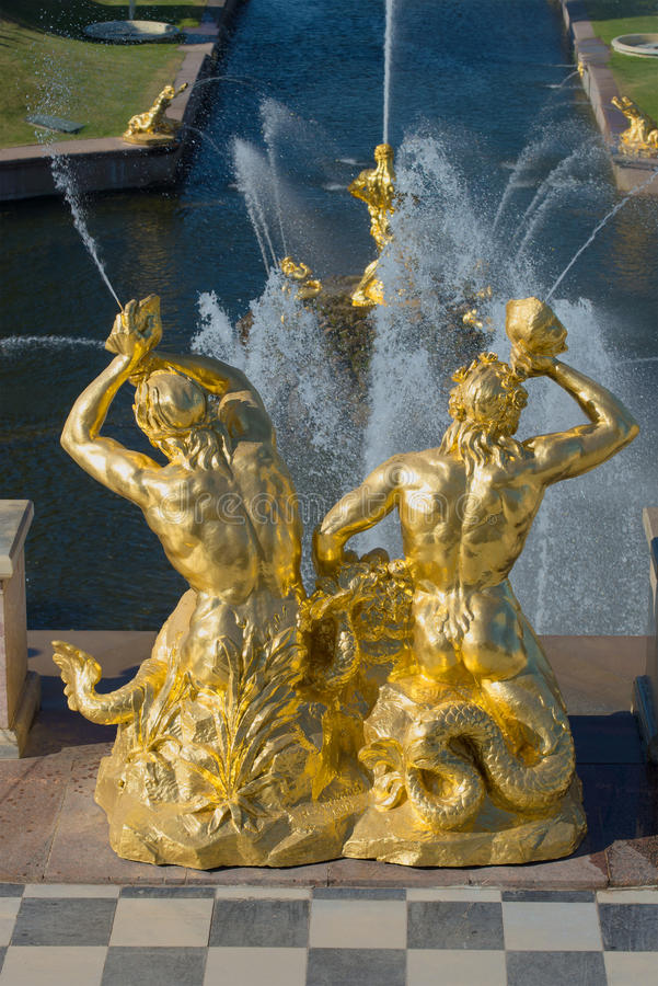 Sculpture of two tritons blowing shell. A fragment of a Large cascade of fountains in Peterhof. Saint Petersburg. SAINT PETERSBURG, RUSSIA - JULY 03, 2015 stock photos