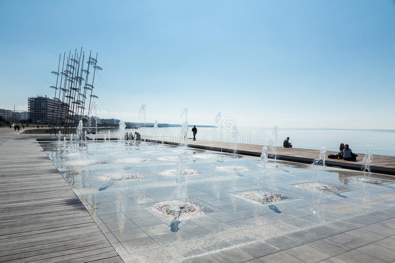 The sculpture Umbrellas by George Zongolopoulos in Thessaloniki. THESSALONIKI, GREECE - OCTOBER 12, 2016: People enjoing new day on a seafront promenade near stock images