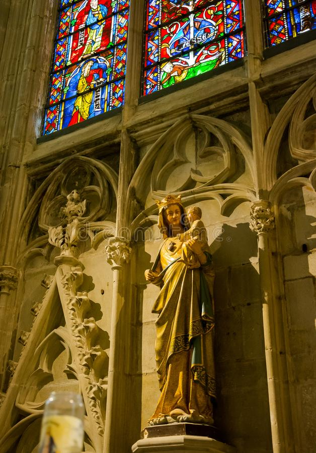 Sculpture of the Virgin Mary with the Child Jesus and Stained Glass in the St. Nazaire Basilica of the city of Carcassonne in royalty free stock photography