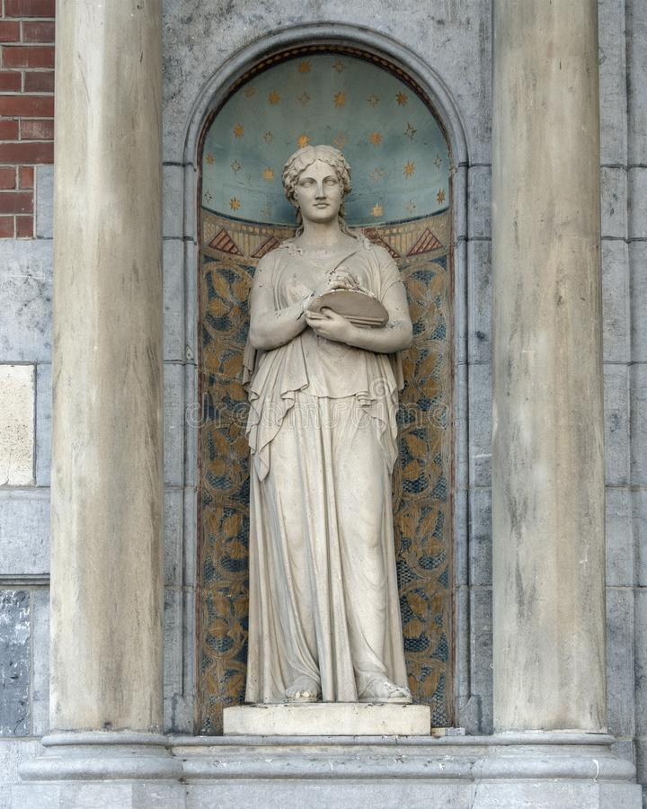 Sculpture of a woman in a Nave between two columns, beside the entrance to the Rijksmuseum, Amsterdam. Pictured is a marble statue of a woman in a nave between stock images