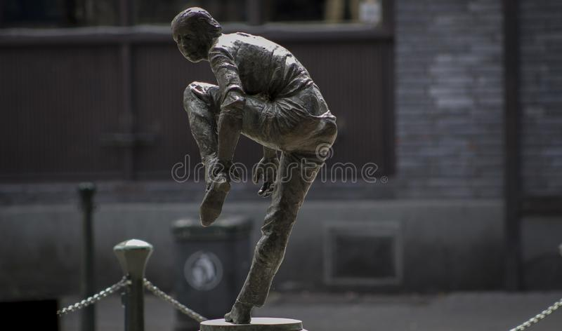 Sculpture of a woman putting on a shoe stock image