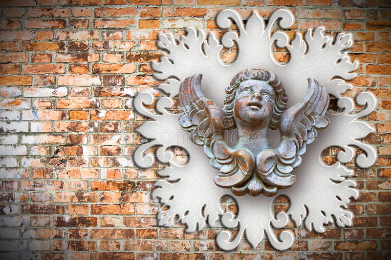 Sculpture of a wooden angel against an old classical plaster frame stock image