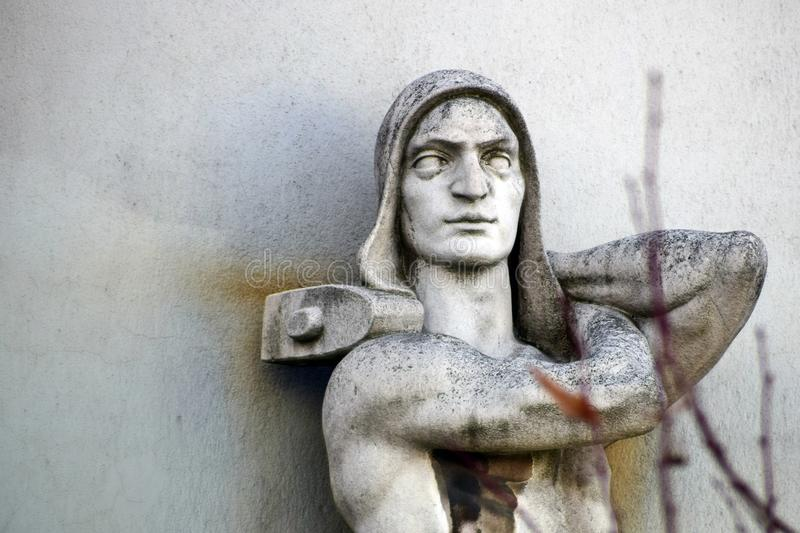 Sculpture of the worker with hammer in hands on the old building facade. royalty free stock image