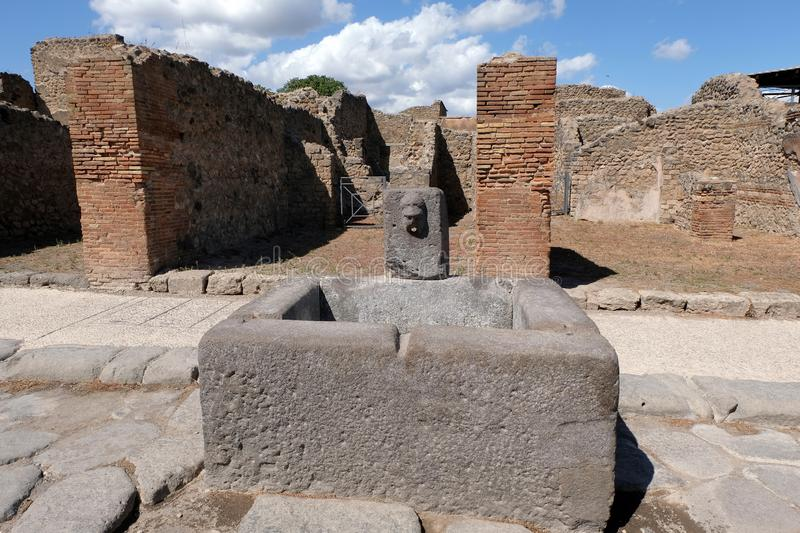 Sculptured fountain in Pompeii. Ruins of Pompeii with a stone fountain with a carved face in the foreground royalty free stock photo
