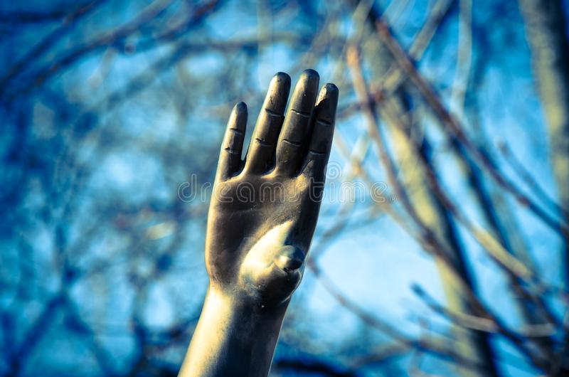 Hand reaching up. Sculptured iron hand reaching up stock image