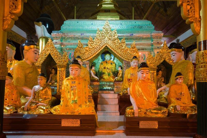 Sculptures d'un Bouddha assis dans un de leurs sanctuaires de la pagoda de Shwedagon Yangon, Myanmar photographie stock