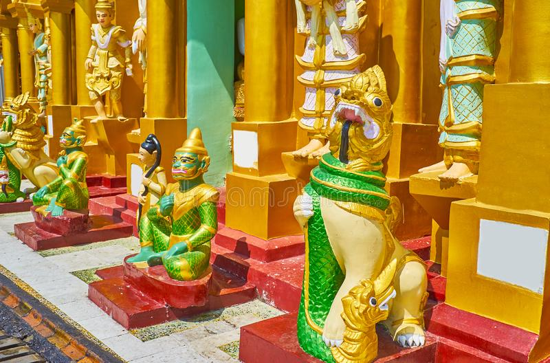The Buddhist art, Shwedagon, Yangon, Myanmar. The sculptures of Nat Spirits and different mythic creatures leogryphs, serpents, belu in front of the stupas in stock image