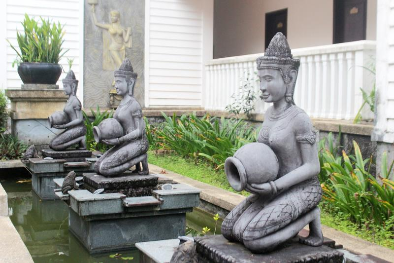 Sculptures of three girls with jugs. Sculptures of three girls-dancers with jugs and frogs, Sihanoukville, Cambodia royalty free stock photos