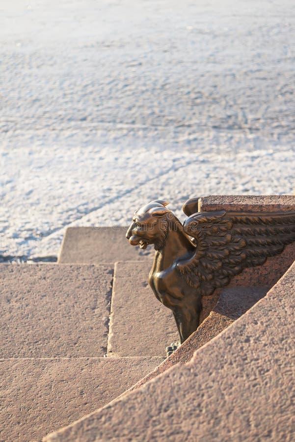 Sculptuur van een bronze Griffin op de voorzijde op de achtergrond van getextureerde sneeuw en graniet royalty-vrije stock foto