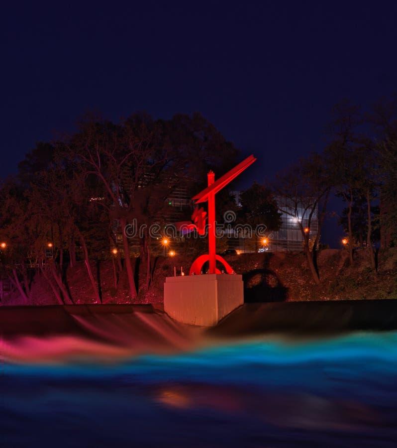 Scultura alle luci del fiume nell'esposizione di un'ora blu fotografie stock
