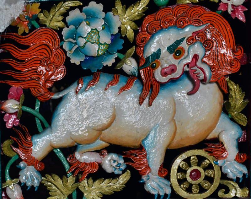 Scultura antica con un'immagine di un leone bianco della neve con una criniera arancio e gli occhi verde smeraldo, il simbolo di  fotografia stock