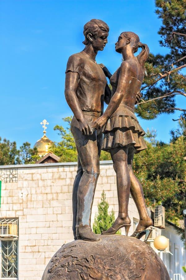 Scultura bronzea di giovani adolescenti su una datazione che sta su un globo e che visualizza amore Simbolo per il giorno di S. V immagini stock libere da diritti