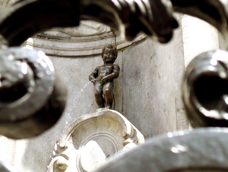 Scultura bronzea di Manneken Pis come vista tramite il recinto del ferro, un piccolo ma punto di riferimento famoso di Bruxelles immagini stock