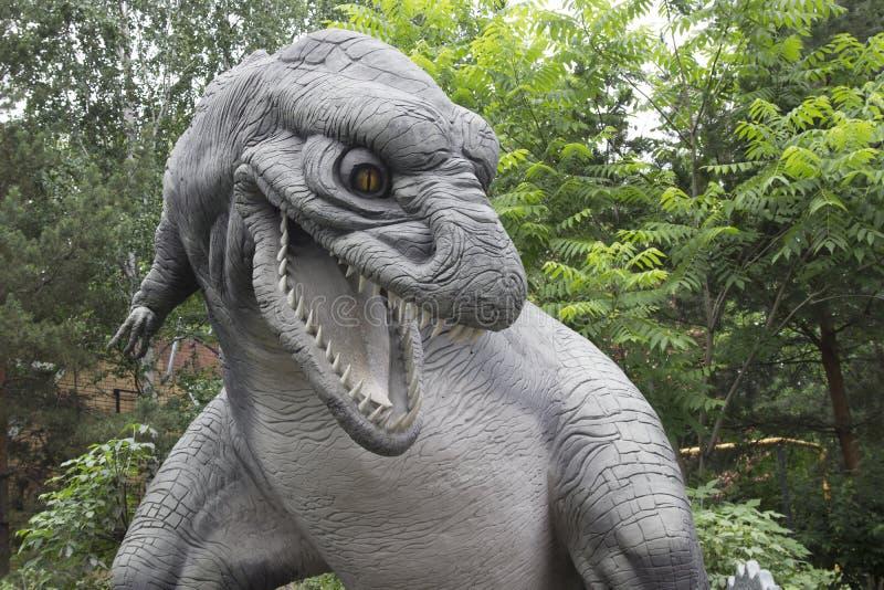 Scultura concreta del Diplodocus nello zoo di Novosibirsk I dinosauri erano turisti superiori usati di tiraggio Scultura del dino fotografia stock