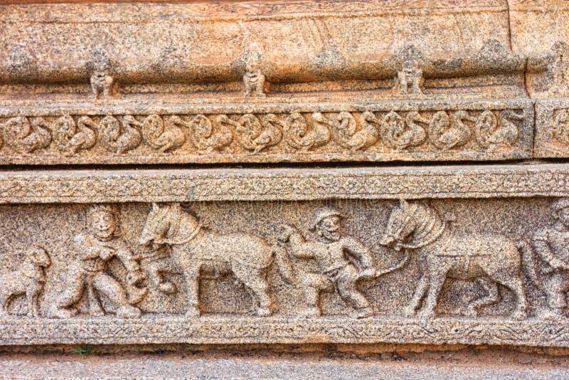 Scultura degli uomini d'affari stranieri in India sulle pareti del tempio immagine stock