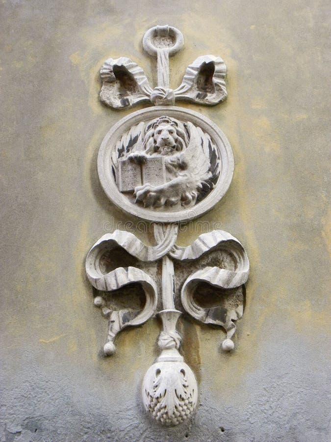 Scultura del leone e della spada sulla parete a Venezia immagine stock libera da diritti