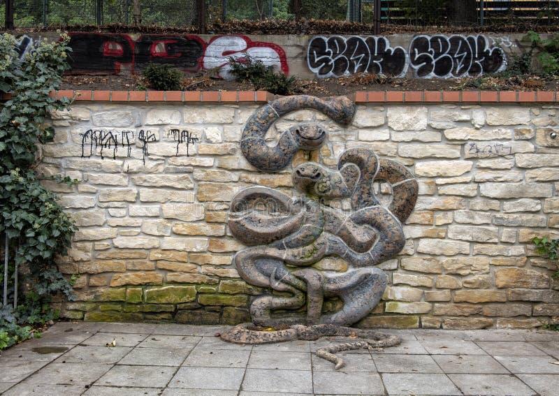 Scultura del serpente sulla parete di pietra, con i graffiti nel fondo, Lesser Town, Praga, repubblica Ceca immagine stock libera da diritti