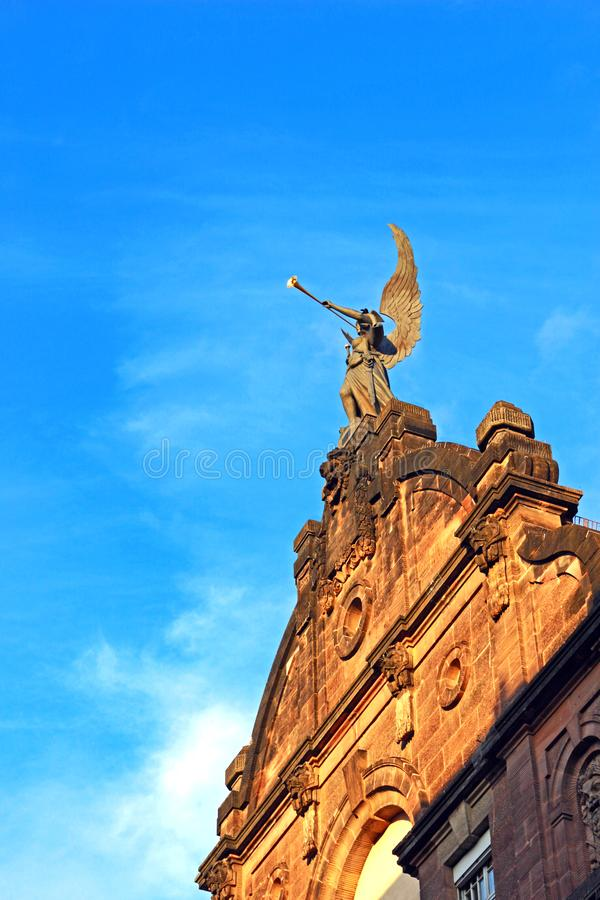 Scultura di angelo con un trombone e una spada immagini stock libere da diritti