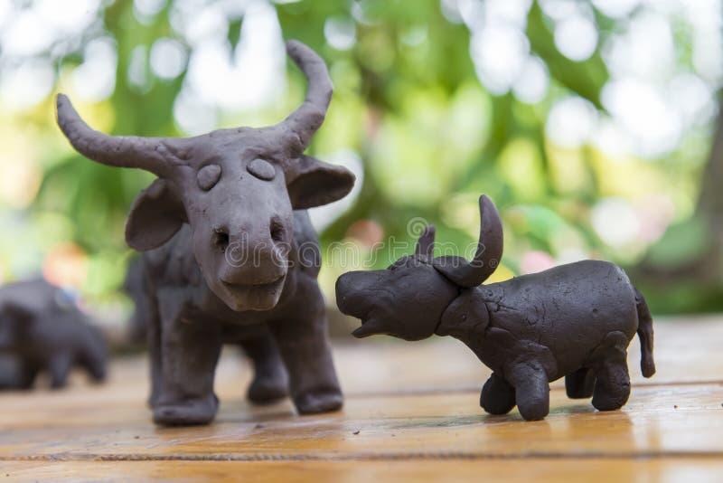 scultura di argilla del bufalo del figlio e del padre su fondo di legno in ou fotografia stock