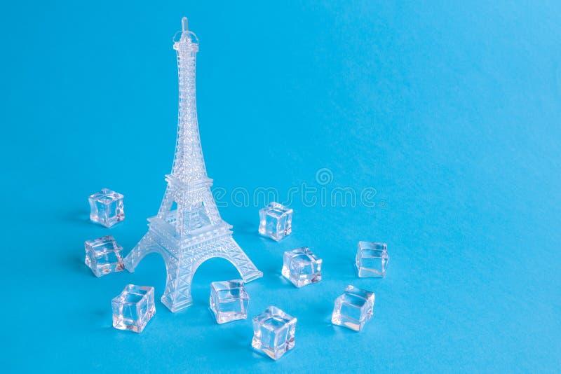 Scultura di ghiaccio dell'estratto dei cubetti di ghiaccio e della torre Eiffel isolato sul blu fotografia stock