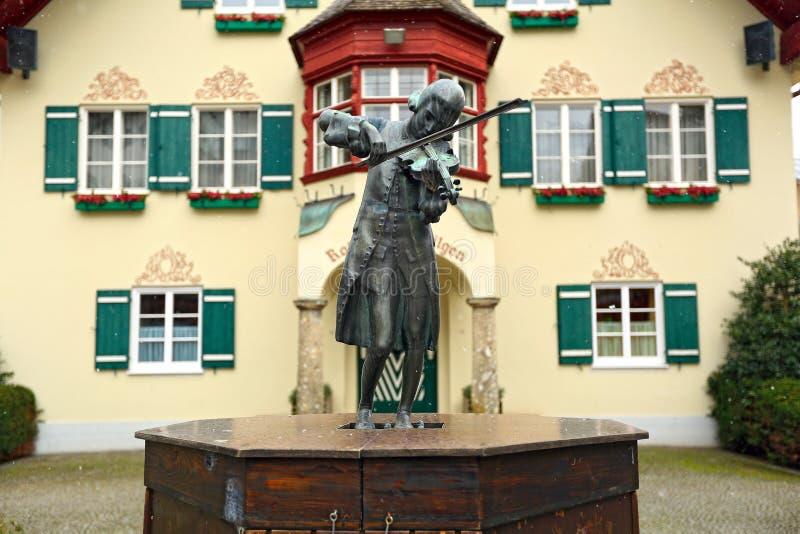 Scultura di giovane Mozart che gioca il violino davanti a municipio Villaggio Sankt Gilgen, Austria fotografia stock libera da diritti