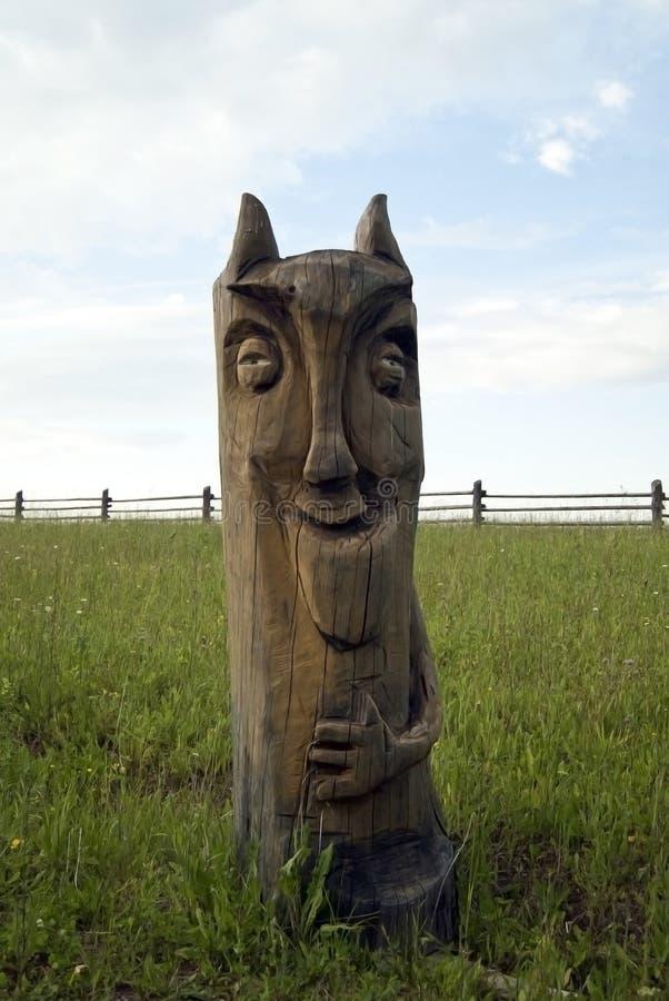 Scultura di legno approssimativa di un diavoletto nel campo all'aperto immagine stock