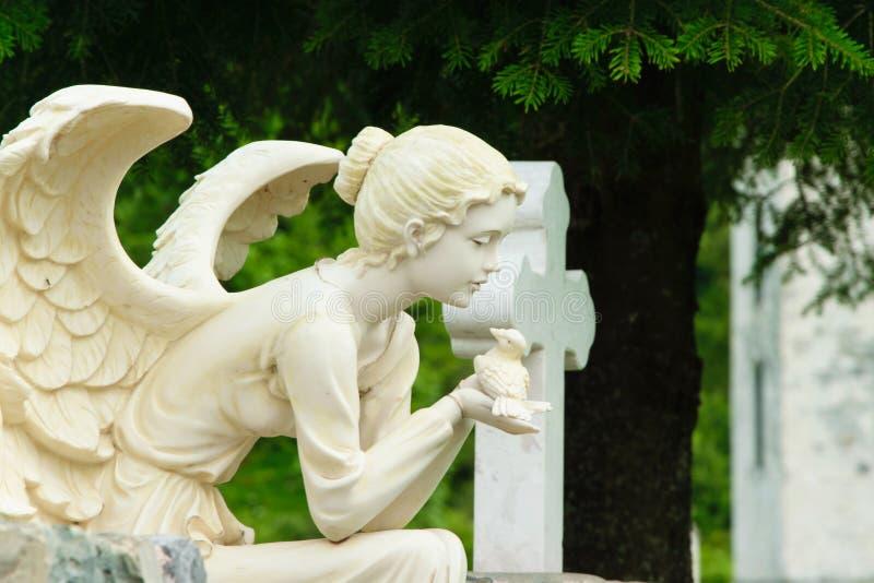 Scultura di marmo dell'angelo femminile che si siede sulla roccia e che tiene un uccello in sue mani fotografia stock