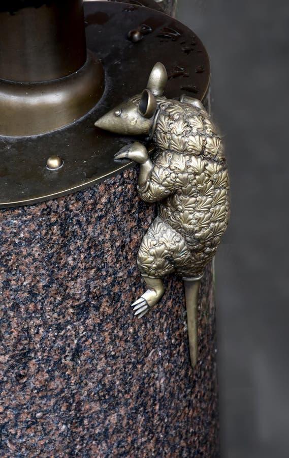 Scultura di piccolo topo che scala una colonna di marmo fotografie stock