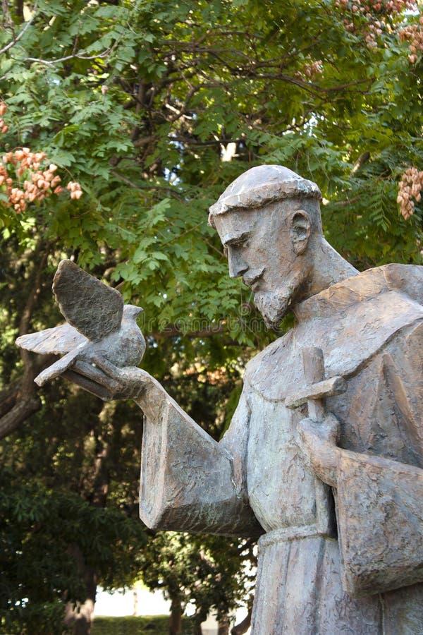 Scultura di St Francis che tiene una colomba e un incrocio immagini stock libere da diritti
