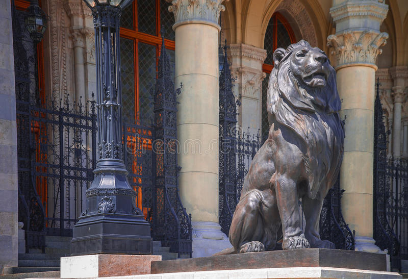 Scultura di un leone vicino alla costruzione del Parlamento a Budapest fotografie stock libere da diritti