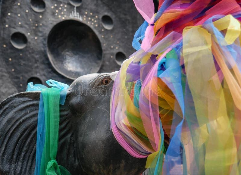 Scultura santa dell'elefante coperta di nastri multicolori in tempio buddista in Tailandia fotografia stock