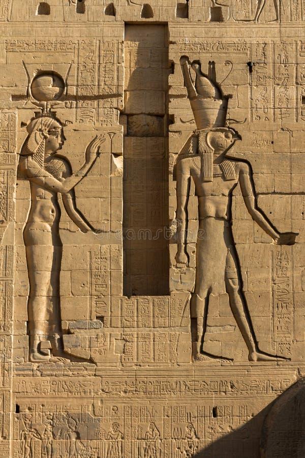 Sculture di sollievo di Hathor e di Osiris sul primo pilone del tempio di ISIS a Philea, Assuan Egitto immagini stock libere da diritti