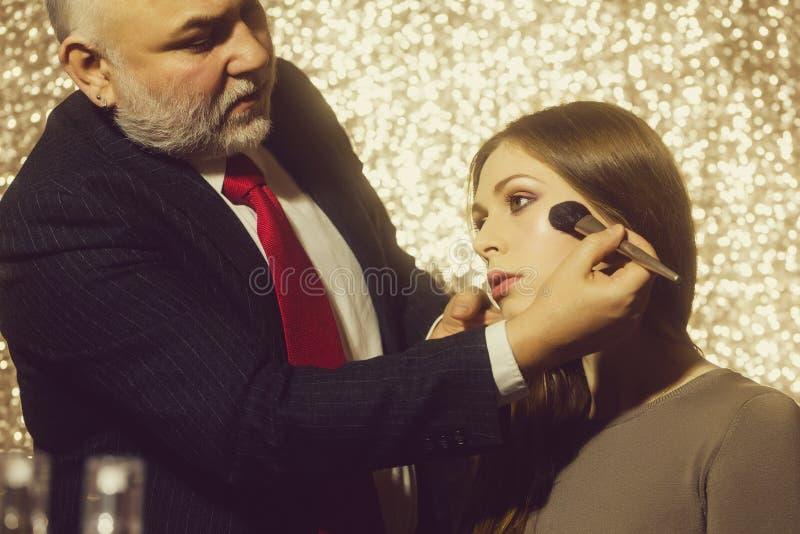 Scuola di trucco Uomo professionale del visagiste che applica polvere sul fronte della ragazza con la spazzola fotografie stock libere da diritti