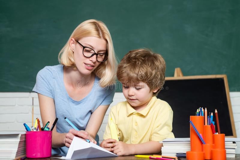 Scuola elementare - istruzione ed imparare concetto del bambino Prima volta alla scuola Bambini felici del banco Madre gli che in fotografia stock